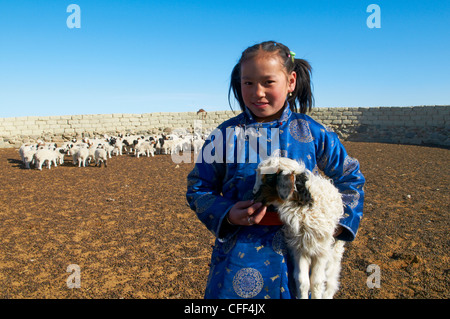 Young Mongolian girl in traditional costume (deel) with her sheep, Province of Khovd, Mongolia, Central Asia, Asia - Stock Photo