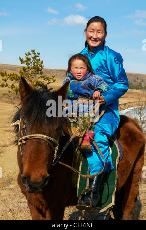 Young Mongolian woman and child in traditional costume (deel) riding a horse, Province of Khovd, Mongolia, Central - Stock Photo
