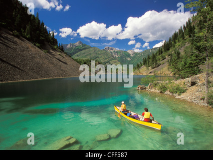 Young couple canoeing on Lower Silver Springs Lake in Elk Valley near Fernie, East Kootenays, British Columbia, - Stock Photo