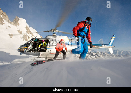 Helicopter and skiers in the mountains, South Tyrol, Italy, Europe - Stock Photo