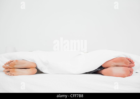 Man and woman's feet in bed turned away from each other - Stock Photo