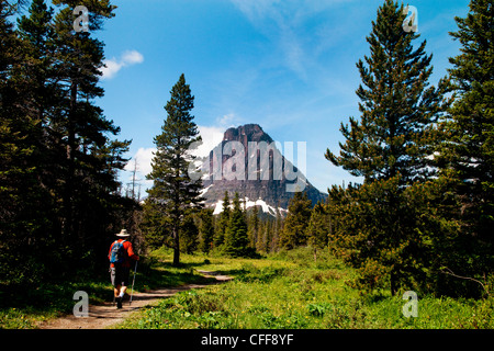 An older man walks along a trial in the middle of the day on a clear blue sky day with a mountain in the distance. - Stock Photo