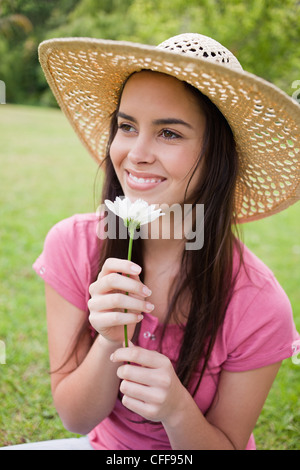 Smiling young woman wearing a hat in a park while smelling a flower - Stock Photo