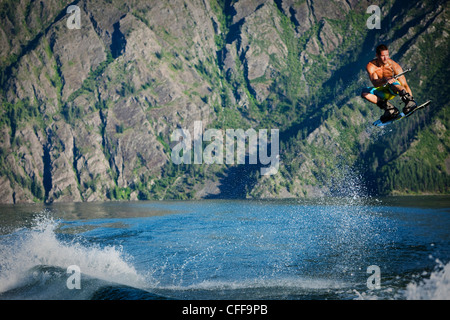 A athletic male wakeboarder boosts over the wake at sunset on a lake in Idaho. - Stock Photo