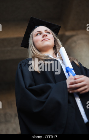 Low-angle view of a graduating student wearing a gown - Stock Photo
