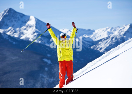 A happy skier smiling raises his arms in celebration of fresh snow with huge mountains behind him in Colorado. - Stock Photo