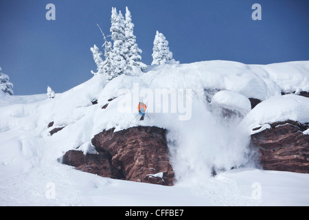 A athletic skier jumping off a cliff in the backcountry on a sunny powder day in Colorado. - Stock Photo