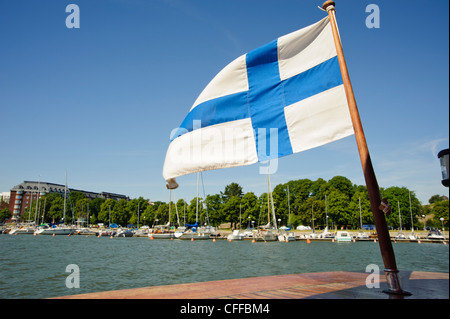 The Finnish flag flies from a boat shuttling between Unisaari island and the Merisatama quayside, Helsinki Finland - Stock Photo