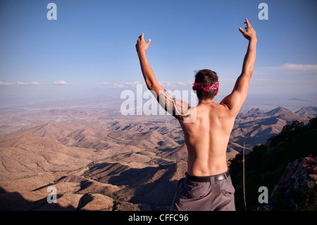 A young man celebrates at the top of The South Rim in Big Bend National Park. - Stock Photo