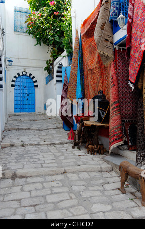 Sidi Bou Said. Tunisia. View of souvenir carpets for sale along narrow cobbled alley with black and white arched - Stock Photo