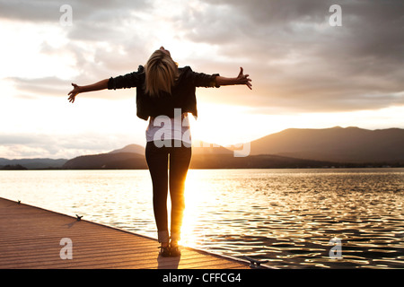 A beautiful young woman looking into the distance holds her arms out embracing the sunset over a lake in Idaho. - Stock Photo