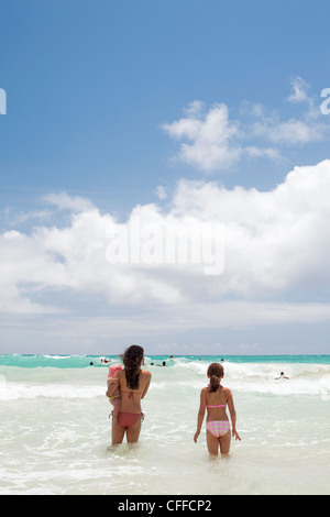 Two girls and a baby going into the sea in Kailua, Hawaii. - Stock Photo