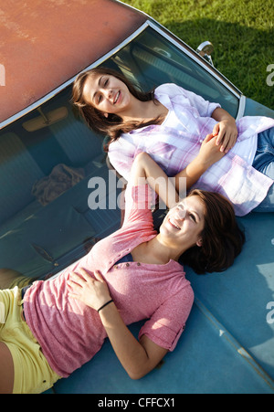 Two sisters lay  on the hood of an old car. - Stock Photo