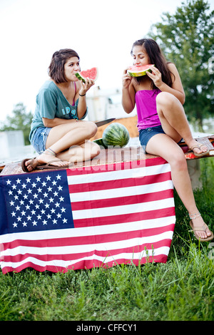Two sisters eat watermelon on a flatbed truck. - Stock Photo