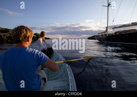A young man and girl row in a Peapod dinghy at sunset toward a classic yacht moored along the coast of Maine. - Stock Photo