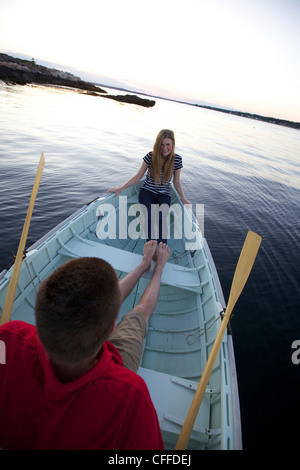 A young man and girl enjoy that sunset in a Peapod dinghy along the coast of Maine. - Stock Photo