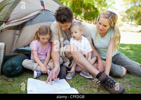 A father shows his kids where they are on a map - Stock Photo