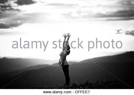 a woman performs a hatha yoga pose on a mountain top stock