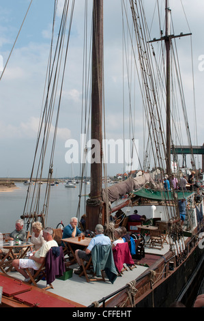 Holidaymakers enjoying a drink on The Albatross, a pub on a boat at Wells Next The Sea, Norfolk, England. - Stock Photo