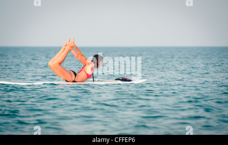 A young woman enjoys her stand up paddle board in the ocean. - Stock Photo