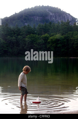 Six-year-old boy plays with a toy boat - Stock Photo