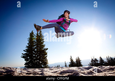 A woman jumping for joy on the Wasatch Crest trail. - Stock Photo