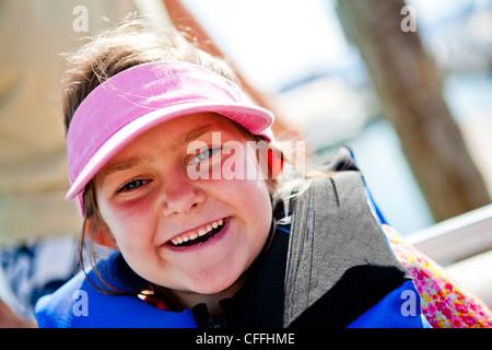 A five year old girl smiles while wearing a pink visor and a life jacket, Bear Lake, Utah. - Stock Photo