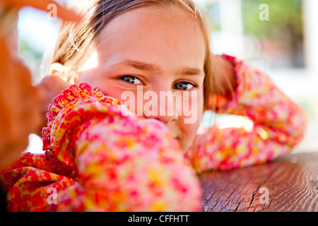 An eight year old girl looks into the camera while sitting at a red picnic table, Garden City, Utah. - Stock Photo