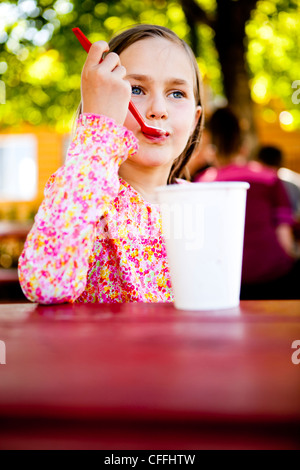 An eight year old girl, eats ice cream while sitting at red picnic table, Garden City, Utah. - Stock Photo