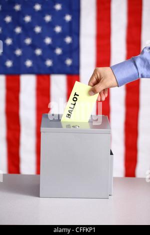 Hand putting ballot into ballot box, voting concept, American flag background - Stock Photo