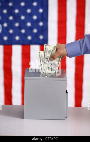 Hand putting money into ballot box, voting and bribery concept, American flag background - Stock Photo