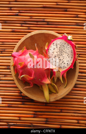 Whole and half dragon fruit in wooden bowl on bamboo background