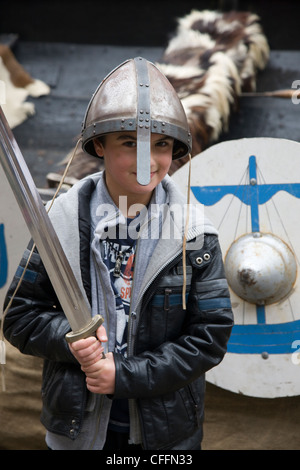 Boy dressed up as a viking warrior with sword, helmet and shield outside the Jorvik Centre in York - Stock Photo