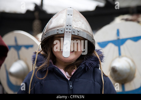 Girl dressed up as a viking warrior with sword, helmet and shield outside the Jorvik Centre in York - Stock Photo