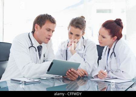 Doctor with tablet showing his colleagues something - Stock Photo