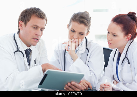 Doctor with tablet computer showing his colleagues something - Stock Photo