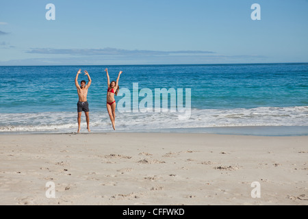 Portrait of couple in swimsuit jumping - Stock Photo