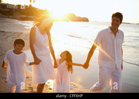 Family walking on the beach while the sun sets - Stock Photo