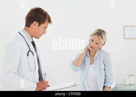 Woman telling her doctor about her neck pain - Stock Photo