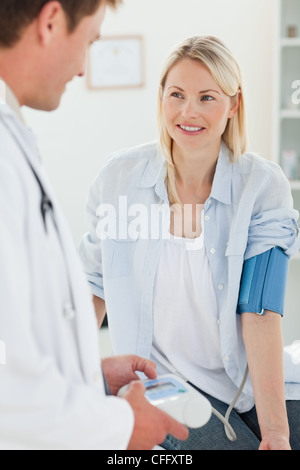 Smiling woman getting her blood pressure measured - Stock Photo
