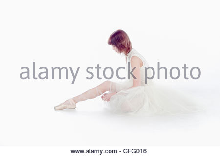 teen girl ballet dancer sitting in a tutu in points on a white background tying her shoe - Stock Photo