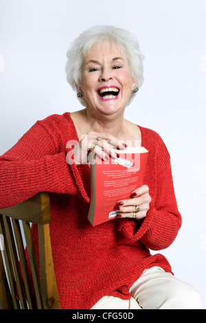 Senior lady in bright clothing smiling and sat on chair with book in hand taken against a white background - Stock Photo