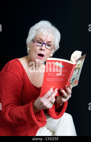 Attractive senior lady in bright clothes with a surprised look on face sitting reading book taken against a black - Stock Photo