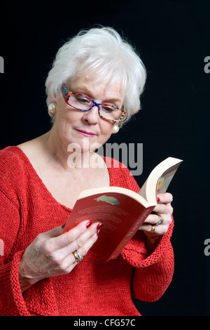 Attractive senior lady in bright clothing sat on chair reading book taken against a black background - Stock Photo