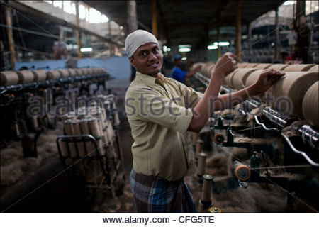 Migrant workers from Bihar turn raw jute into bolts of golden fiber inside the Hastings Jute Mill. - Stock Photo