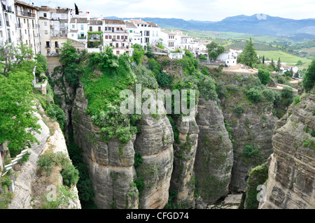 Spain - Malaga province - Ronda - old town above the El Tajo gorge of rio Gudalevin - backdrop Serrania de Ronda - Stock Photo