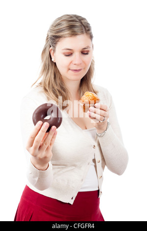 Hungry woman holding delicious sweet muffin and chocolate donut, isolated on white background. - Stock Photo
