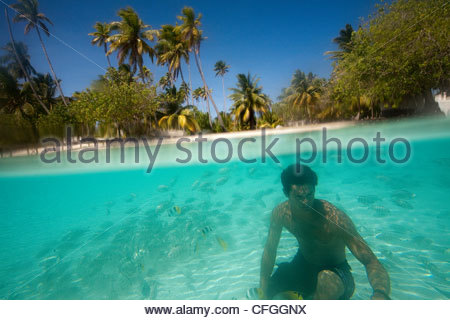 A black pearl oyster diver at a pearl farm surrounded by fish. - Stock Photo