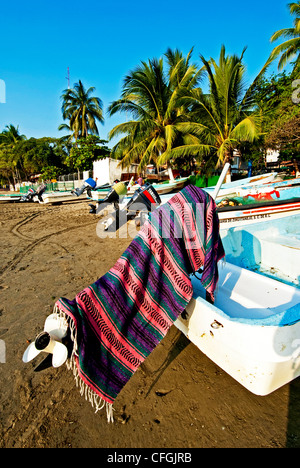 Fishing boat on the beach with a typical Mexican blanket covering the engine, Zihuatanejo, Mexico - Stock Photo