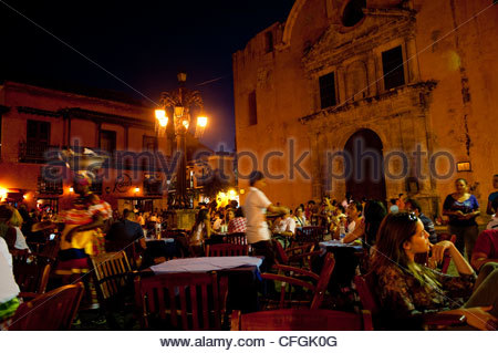 People stroll through an illuminated courtyard with a cafe at night. - Stock Photo
